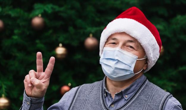 Рождественский кусок. крупным планом портрет старшего человека в шляпе санта-клауса и медицинской маске с эмоциями. на фоне елки. коронавирус пандемия