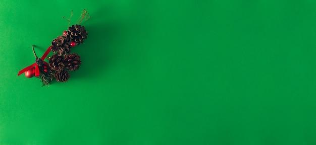 緑の背景に赤いリボンとクリスマスの松ぼっくり。スペースをコピーします。セレクティブフォーカス。