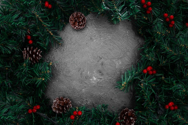 Christmas pine leaves frame on a grunge gray background