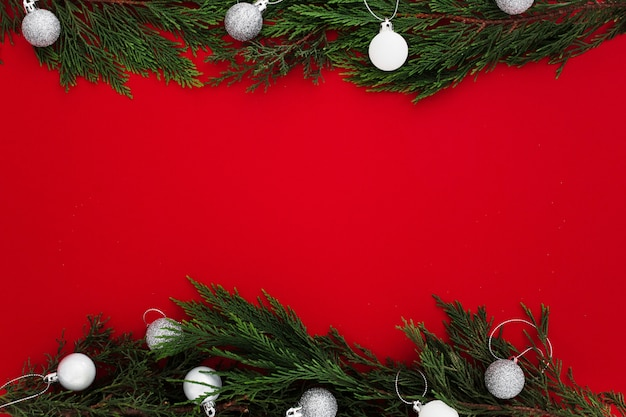 Christmas pine leaves on a red background with a blank note