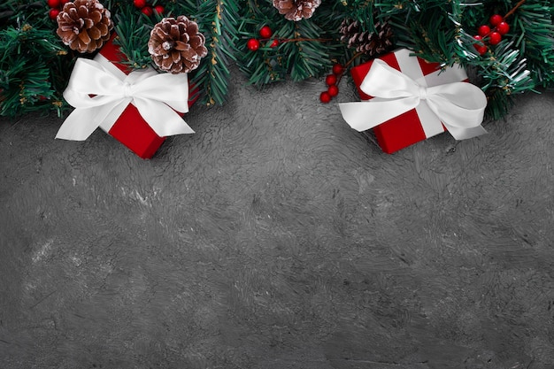 Christmas pine leaves with red boxes on a grunge gray background