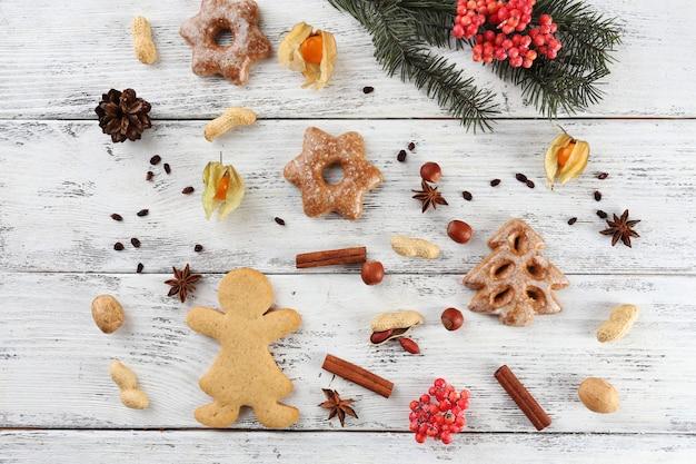 カラーの木製の背景にスパイスとクッキーとクリスマス松の小枝