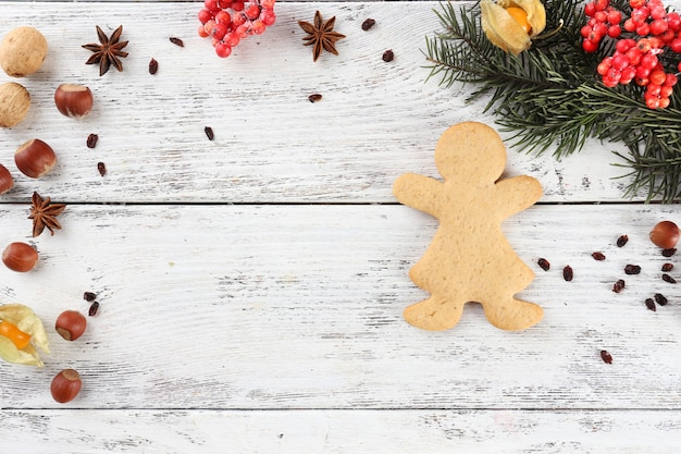 カラーの木製の背景にスパイスとジンジャーブレッドとクリスマス松の小枝