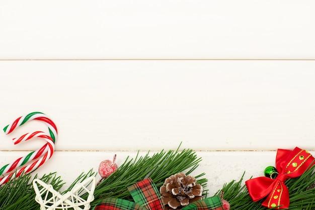 白い木製の背景にクリスマス松の木の枝。キャンディケイン、クリスマスの弓、松ぼっくり。