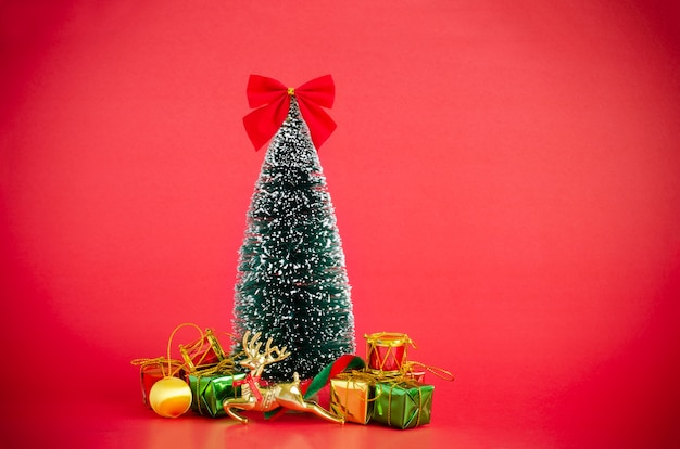 Christmas pine tree cover with snow decorating with xmas ornaments over red background