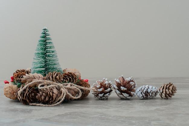 Albero di pino di natale e corona su marmo.