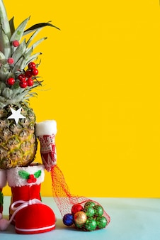 Christmas pineapple in santa boots, winter mittens and a bag of chocolate colored candies