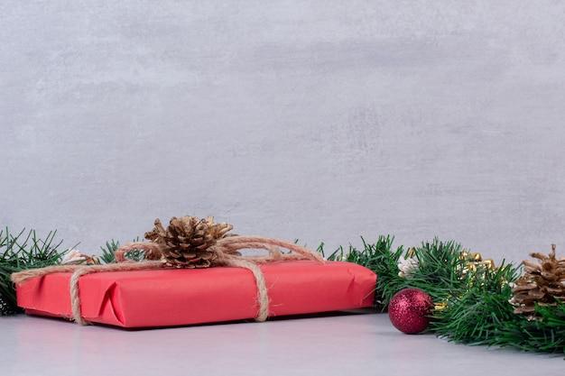 Рождественская игрушка из сосновой шишки с красной коробкой на серой поверхности