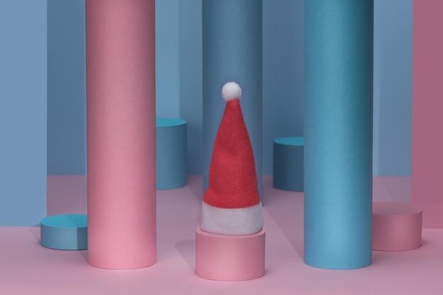 Рождественский розовый и синий фон, пьедестал в шляпе санта-клауса
