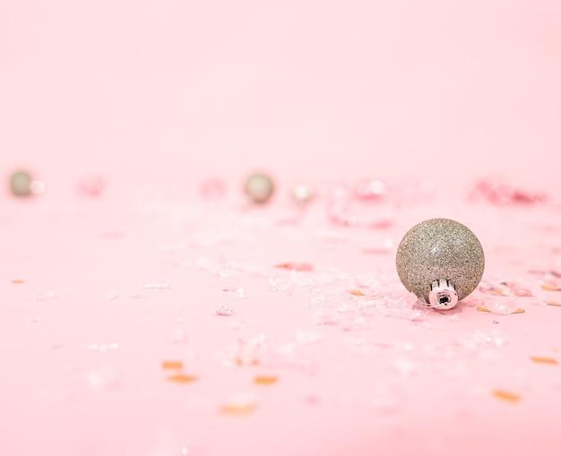 흐릿한 배경에 크리스마스 트리를 위한 공이 있는 크리스마스 분홍색 배경, 복사 공간.