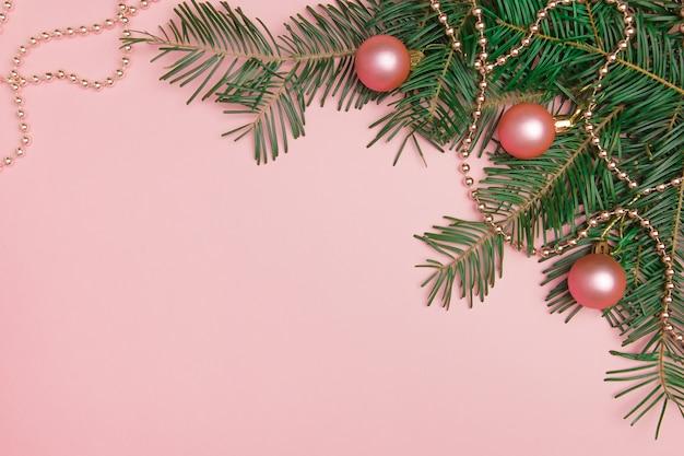 Рождественский розовый фон с еловой веткой розовые шары и бусы