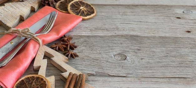 素朴な木製のテーブルのクリスマスの場所の設定はコピースペースでクローズアップ