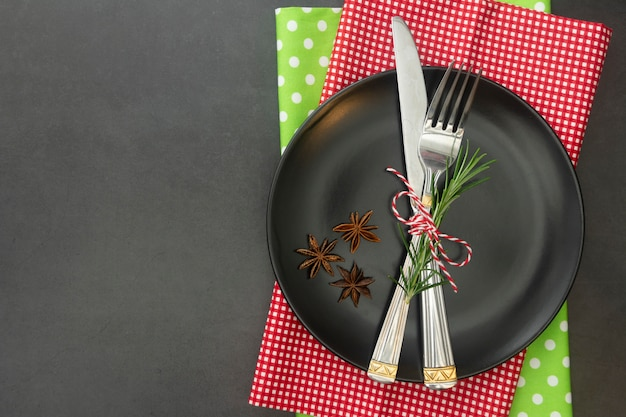 Christmas place setting with black plate, fork and knife.