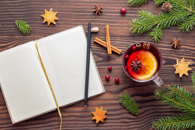 Christmas planning in a paper notebook with a mug of mulled wine at a wooden table