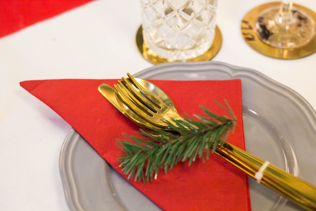 Christmas plate and goldware with red cloth with branch of fir tree