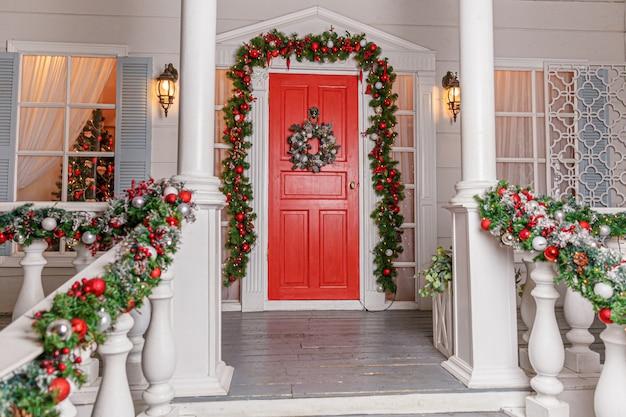 Идея украшения рождественского крыльца. вход в дом с красной дверью, украшенной к праздникам.