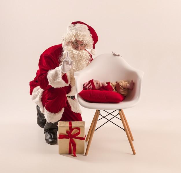 Ritratto di natale della piccola neonata sveglia, vestita in abiti natalizi, girato in studio, orario invernale
