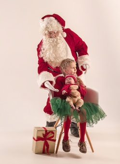 Christmas portrait of cute little newborn baby girl, pretty teen sister, dressed in christmas clothes and man wearing santa costume and hat, studio shot, winter time. the christmas, holidays concept