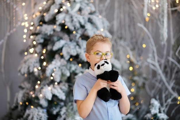 Christmas portrait of happy child boy with big glasses holding toy bear indoor studio