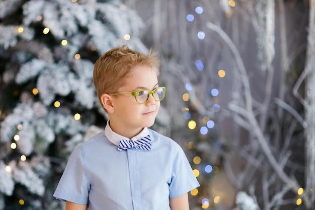 Christmas portrait of happy child boy with big glasses indoor studio