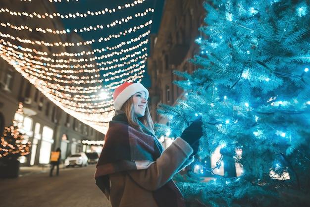 Рождественский портрет улыбающейся девушки в теплой одежде вечером на украшенной улице в огнях возле елки