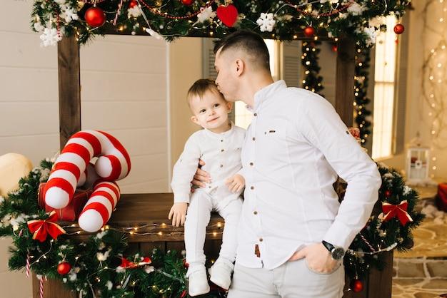 Портрет рождества молодого привлекательного папы с маленьким сыном на предпосылке бара рождества. новый год и рождество концепция