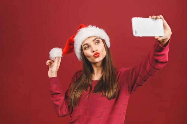 サンタクロースの帽子をかぶって、笑顔で携帯電話でselfieを作る美しい少女のクリスマスの肖像画