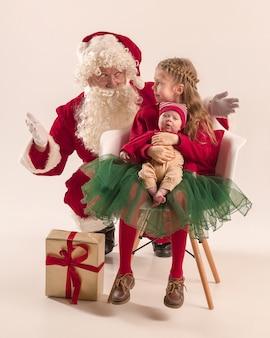 귀여운 작은 신생아 아기 소녀, 예쁜 사춘기 자매의 크리스마스 초상화, 크리스마스 옷과 산타 의상과 모자, 스튜디오 촬영, 겨울 시간을 입고 남자를 입고. 크리스마스, 휴일 개념