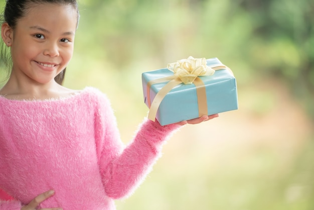 Рождественский портрет счастливого улыбающегося ребенка маленькой девочки с подарочной коробкой около дерева зеленой ветви. зеленые листья боке не в фокусе фон из природы леса.