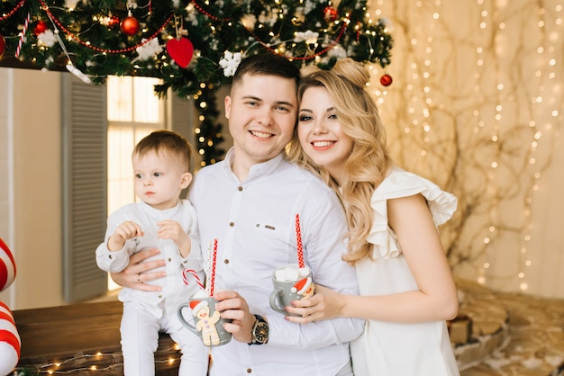 Christmas portrait of young parents with a young son on the background of a christmas bar. new year and christmas concept