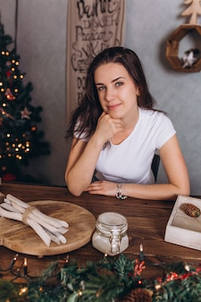 Christmas portrait of young pretty brunette woman at cozy home