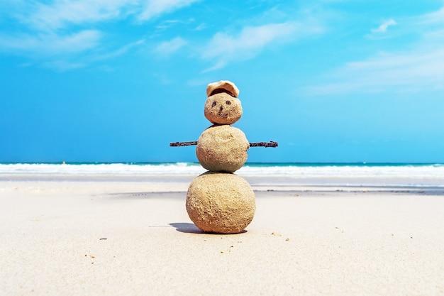 海の夕日のビーチで赤いサンタクロースの帽子をかぶったクリスマスポジティブサンディスノーマン。暑い国の目的地の概念での年末年始の割引