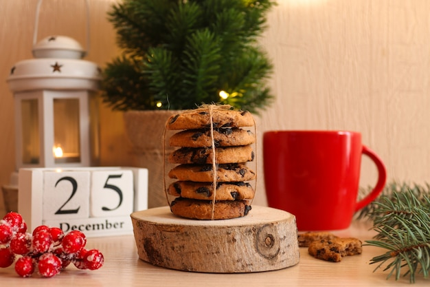 Christmas postcard with chocolate cookies on wooden stand red cup christmas tree latern and calendar