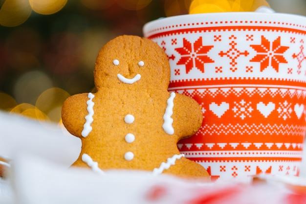 クリスマスの飾りとジンジャーブレッドマンの赤いマグカップが付いているクリスマスのポストカード