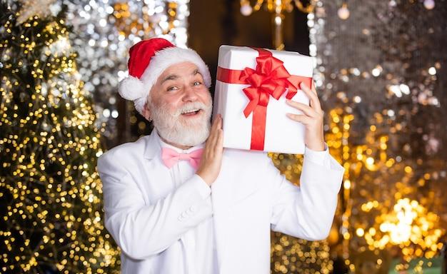クリスマスの準備。シニア男性サンタ帽子はギフトボックスを保持します。あごひげを生やしたビジネスマンが存在します。休日の装飾のイルミネーション。このクリスマスを幸せにしてください。あけましておめでとう。安いクリスマスプレゼントとビジネス報酬。