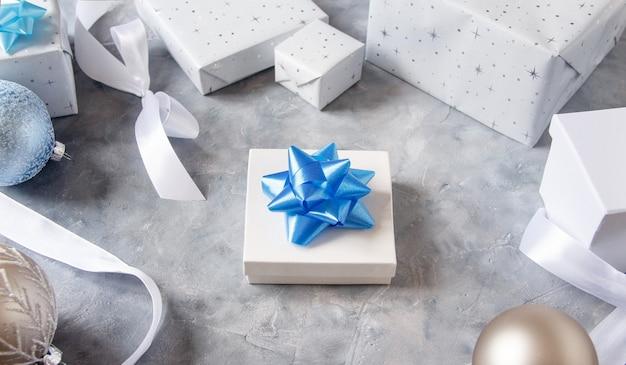 Рождественский подарок и украшения крупным планом на сером столе