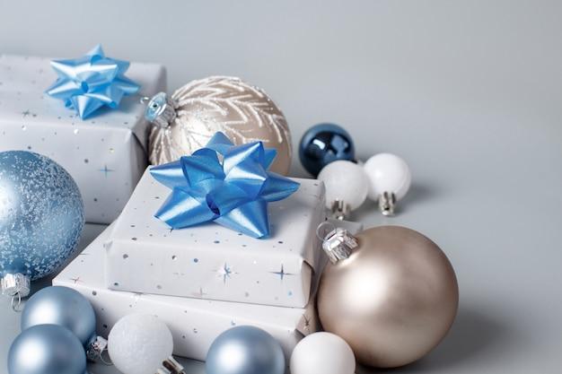 Рождественский подарок и украшения крупным планом на сером