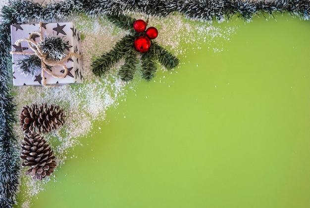 크리스마스 선물과 하얀 눈이 있는 녹색 배경의 장식. 복사 공간