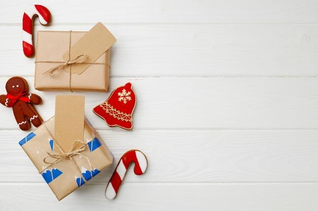 Рождественский подарок и праздничные пряники на деревянных фоне