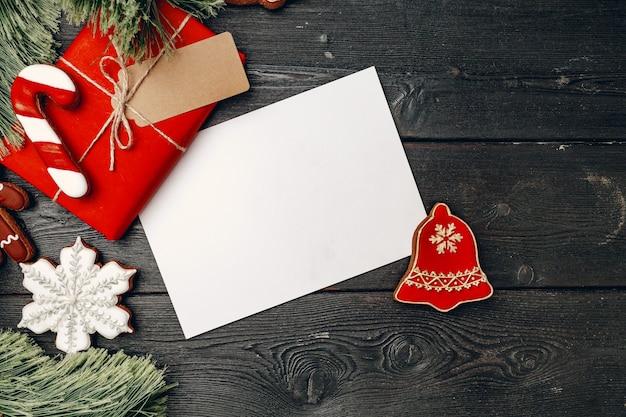 クリスマスプレゼントと木製の背景にお祝いのジンジャーブレッドクッキー