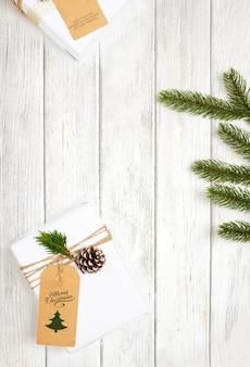 Рождественский подарок и украшение из сосновых листьев на белом деревянном столе