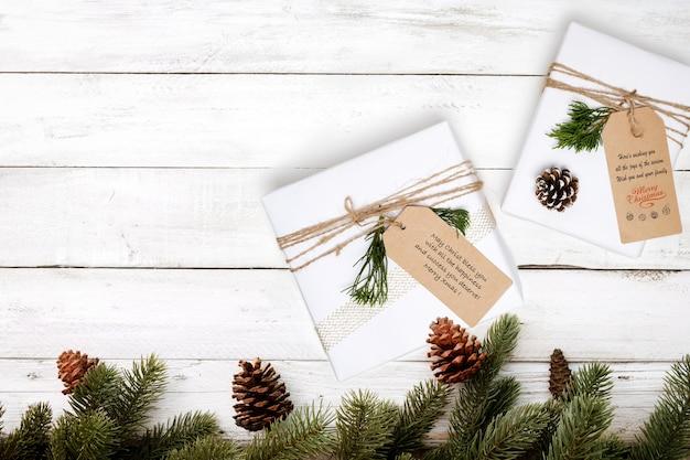 Рождественский подарок и украшение сосновых листьев на белом деревянном столе.