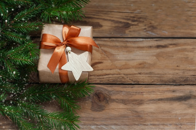 Christmas present box with fir branches and holiday decoration on wooden background