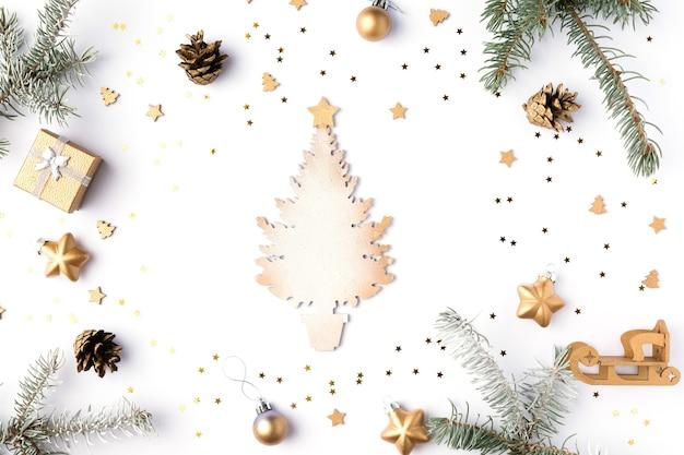 白い背景に金の装飾、ボール、星、円錐形のクリスマスプレゼントボックス。新年のコンセプト、休日の構成、冬のフラットレイ。上面図。スペースをコピーします。