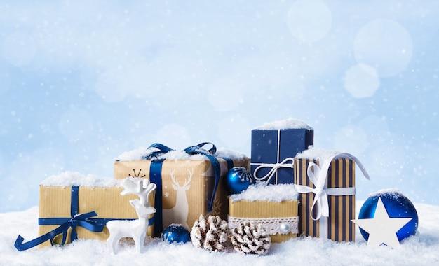 雪に覆われた青いボール、つまらないもの、白い鹿のクリスマスプレゼントボックス。コピースペースと冬のクリスマス水色の風景の背景。