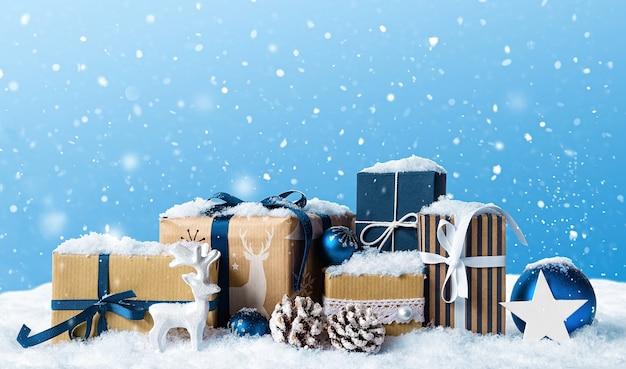 雪に覆われた青いボール、つまらないもの、白い鹿のクリスマスプレゼントボックス。冬のクリスマス水色の風景の背景