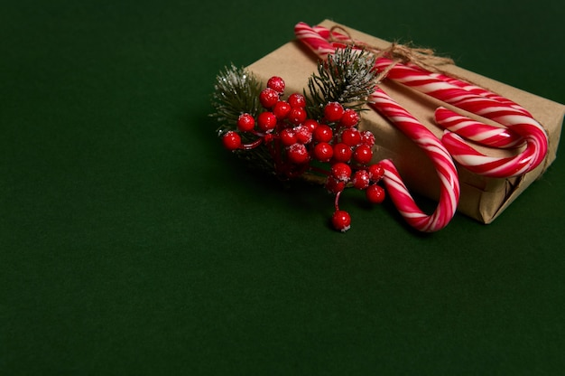 Christmas present in craft wrapping gift paper decorated with holly and sweet sugary striped white and red lollipops candy canes laid out in the corner of copy space on dark green background