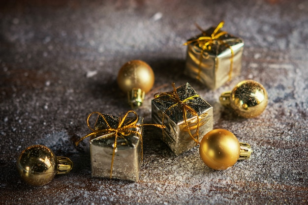 Christmas present mini golden boxes in the snow background. winter holiday background.