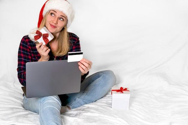 크리스마스 선물. 선물 상자와 장난스럽게 웃는 여자