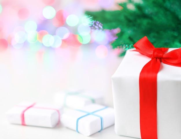 モミの木とデフォーカスライトの最小限の構成の背景にクリスマスプレゼント